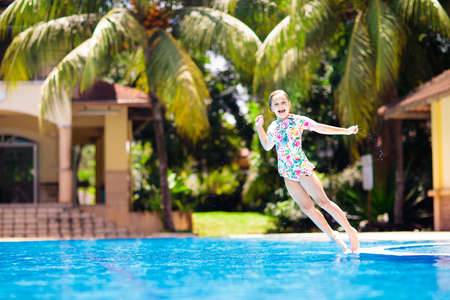 Child playing in swimming pool. Summer vacation with kids. Little girl jumping into water during exotic holiday in tropical island resort. Children swim. Active outdoor sport for preschooler.