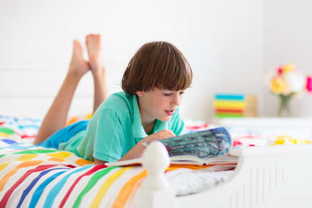 Child reading book in bed in white sunny bedroom with window. Kids read books. Bedding and textile for children nursery. Kid boy with toy. Nap and sleep time. Student doing homework. Banque d'images
