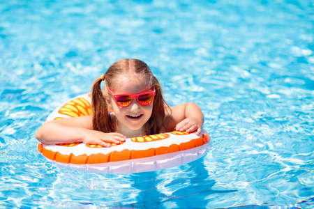 Child in swimming pool floating on toy ring. Kids swim. Colorful yellow float for young kids. Little girl having fun on family summer vacation in tropical resort. Beach and water toys. Sun protection.