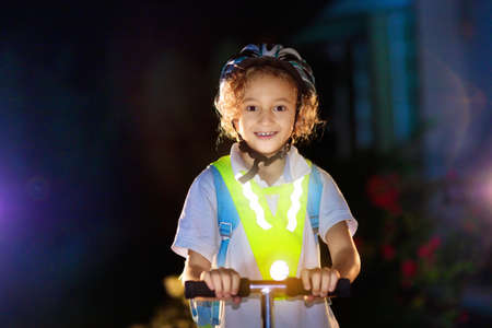 Kid in reflective vest in darkness. Safety on dark city streets for school children. Safe way home at night or in the evening. Fluorescent stripes on kids clothing and backpack. Boy walking at dusk. Standard-Bild
