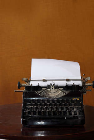 old typewriter with blank paper on a table photo