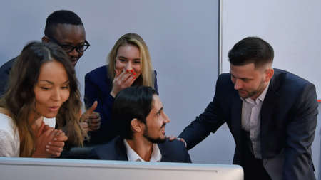 Group of multiracial business team shoked with result, surprised, smiling and looking at laptop computer. Professional shot in 4K resolution. 085. You can use it e.g. in your commercial video, business, presentation, broadcast video.