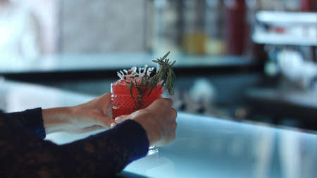 sweet vermouth: female hands holding red cocktail in the bar