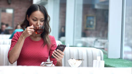 Asian woman looking at cellphone and drinking tea in cafe Imagens