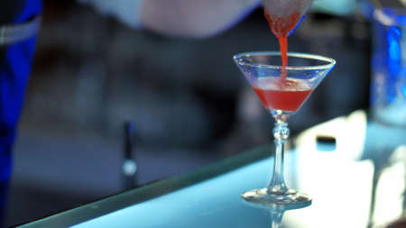 Bartender pouring mixed liqueur into prepared glass through cocktail strainer Stock Photo