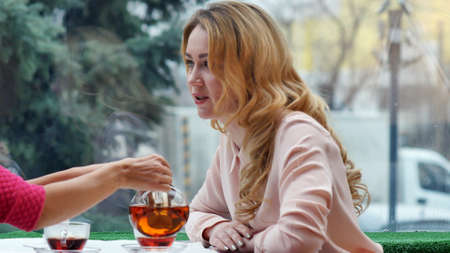 to contemplate: Blonde enjoying hot tea and talks with friend in cafe