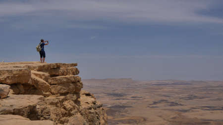 Young man standing on cliff edge and taking panoramic photo of the desert on his phone