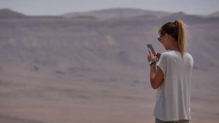 Young woman taking panoramic photo of the desert crater on her phone Archivio Fotografico