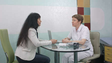 Female doctor looking in client eyes and talking positively