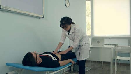 Doctora haciendo examen abdominal en paciente masculino Foto de archivo