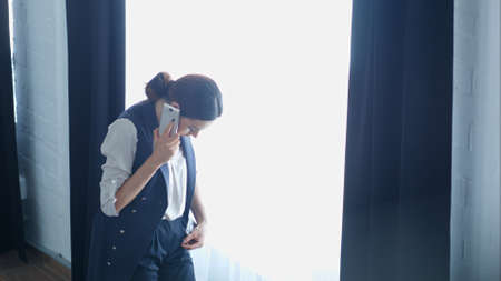 Young proud businesswoman is talking on her mobile phone with client, while standing near office window 写真素材