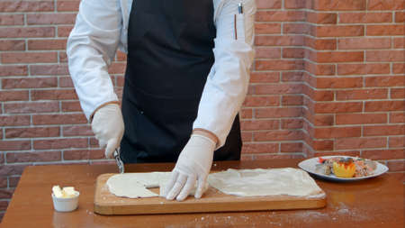 Lo chef aveva la sfoglia per affettare la pasta con il coltello a rullo Archivio Fotografico