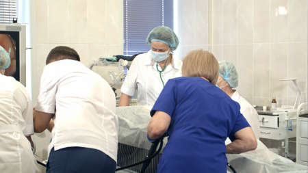 Group of doctors and nurses looking at the monitor during surgical operation