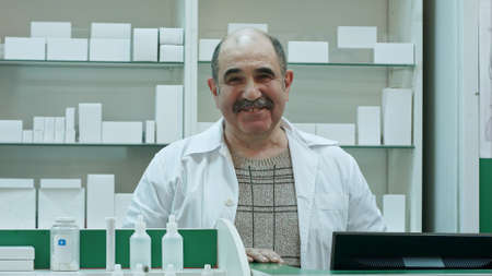 Portrait of senior pharmacist smiling and talking to a camera