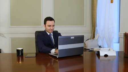 European worker typing on keyboard and looking at monitor of laptop Stockfoto