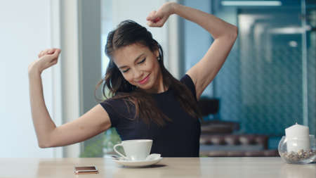 Young bored brunette yawning and stretching and drinking coffee in a cafe Stock Photo
