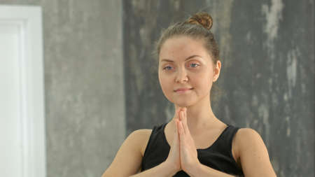 Ypung blonde woman namaste practicing yoga in a studio indoors