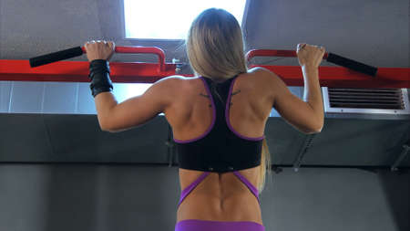 Blonde woman doing pull ups at the gym. Back view. Banque d'images