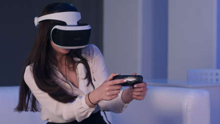 Woman wearing virtual reality device and playing video game with gamepad