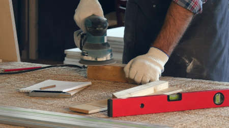 Man working with wooden planck and electric planer in workshop.