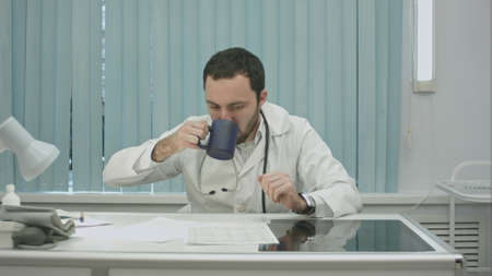 tired  from work, bearded doctor drink from cup and continue woking with documents and x-rays