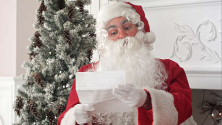Santa Claus sitting in his workshop reading a letter Stock Photo