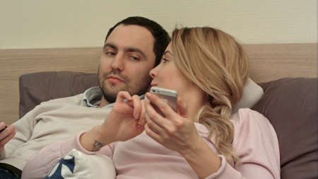 Attractive woman lying in bed texting at mobile phone smiling, while her partner pry at the screen