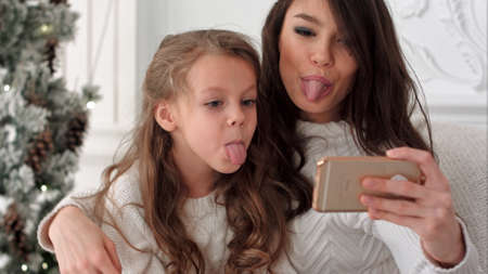 Cheerful young mother and her daughter making comic xmas selfies and showing tongues 스톡 콘텐츠