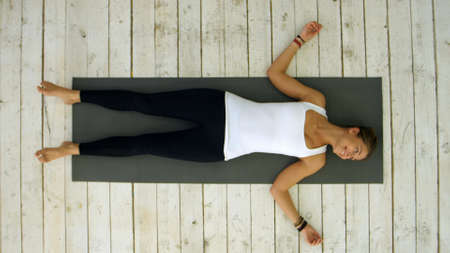 Attractive young woman working out at home, doing yoga exercise, lying in Shavasana Corpse or Dead Body Pose , resting after practice, meditating, breathing
