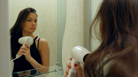 Young attractive girl dries hair with a hairdryer in a hotel bathroom