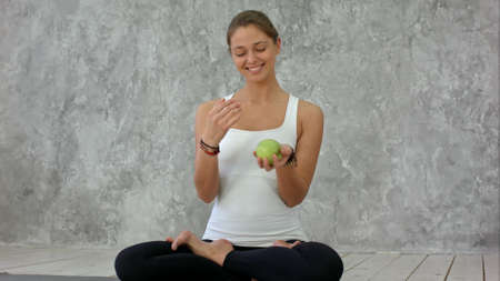 Beautiful smiling woman holding green apple, jungle with it, sitting in lotus pose