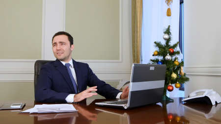 Shocked young businessman is getting fired by his employee, but turn into a joke trying to throw a ball pen, because it is Christmas time Imagens