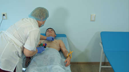 Nurse preparing patients chest to attach electrode pads for ECG