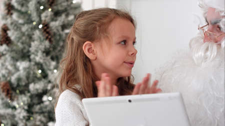 Santa with tablet listenting to a little girl describing presents she wants for Christmas Reklamní fotografie