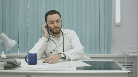 male doctor speaking on cellphone at modern hospital indoors Archivio Fotografico