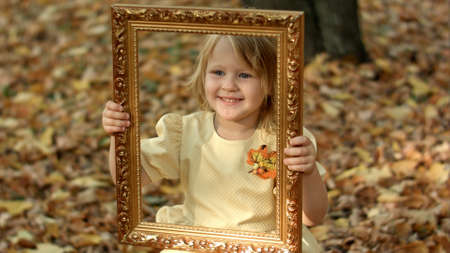 Girl posing with picture in autumn park