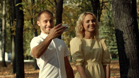 Smiling couple making selfie in autumn park Archivio Fotografico
