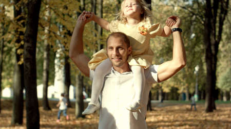 Little girl in the arms of his father walk in autumn park