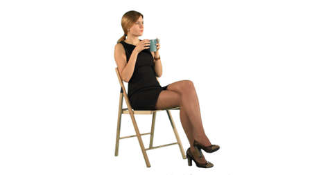 A young attractive woman with a cup of coffee or tea on laptop on white background isolated