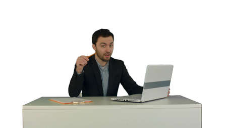 Happy businessman sitting in office with laptop and say on camera on white background isolated
