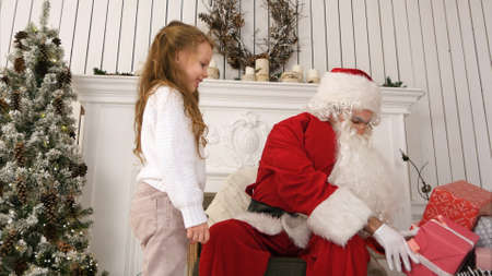 Little girl bringing a present for Santa and hugging him in his Christmas workshop