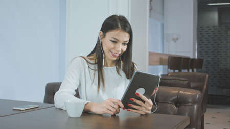 Beautiful young woman using a tablet pc to make a video call while sitting in a cafe