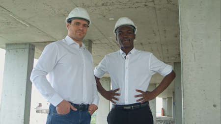 Architectural team smiling at the camera with hard hats Stock fotó