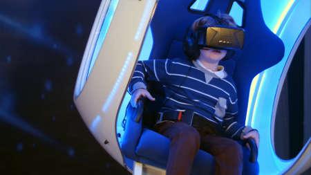 Kleine jongen ervaart virtual reality zittend in interactieve bewegende stoel