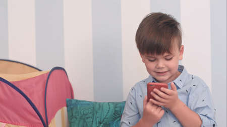 Excited little boy reading a message on his phone Stock Photo