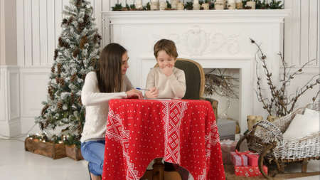Young mother helping her little son to write a letter to Santa Claus Banco de Imagens