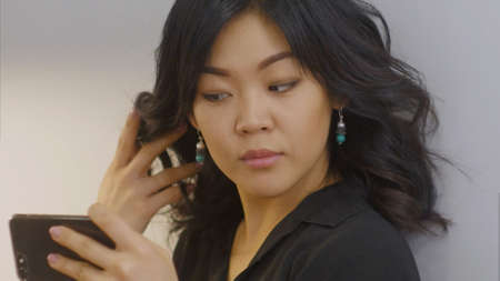 Young asian woman takes selfie in new designed earrings using smartphone