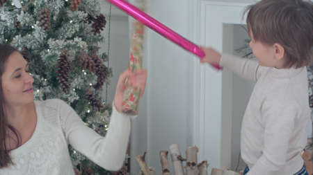 Happy mother and son having wrapping paper sword fight near the Christmas tree