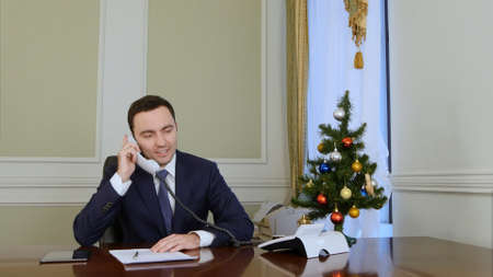 Smiling businessman picking up the phone and congratulates business colleagues with Christmas Stock fotó