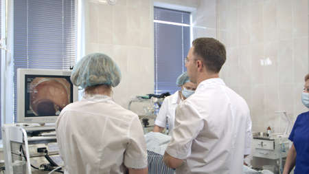 Team of doctors using endoscopic equipment during operation